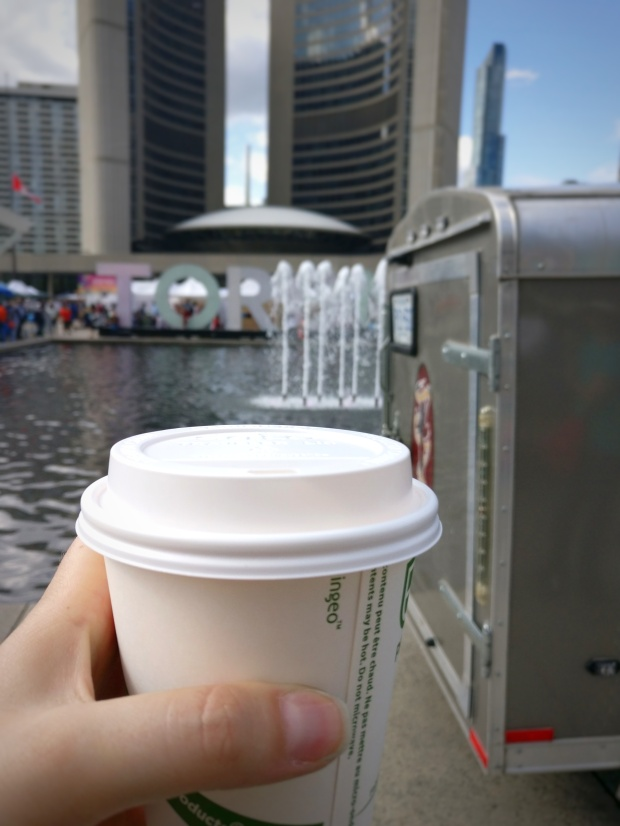 latte cup with toronto city hall in background